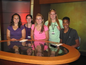 Students try out the anchor desk in the Williams Hall TV studio.